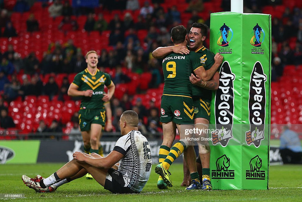 Josh Papalii (R) of Australia celebrates scoring a try with Cameron Smith as Kane Evans (L) of Fiji sits forlonly during the Rugby League World Cup Semi Final match between Australia and Fiji at Wembley Stadium on November 23, 2013 in London, England.