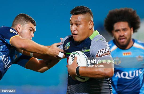 Josh Papalii of the Raiders breaks the tackle of Ashley Taylor of the Titans during the round six NRL match between the Gold Coast Titans and the...