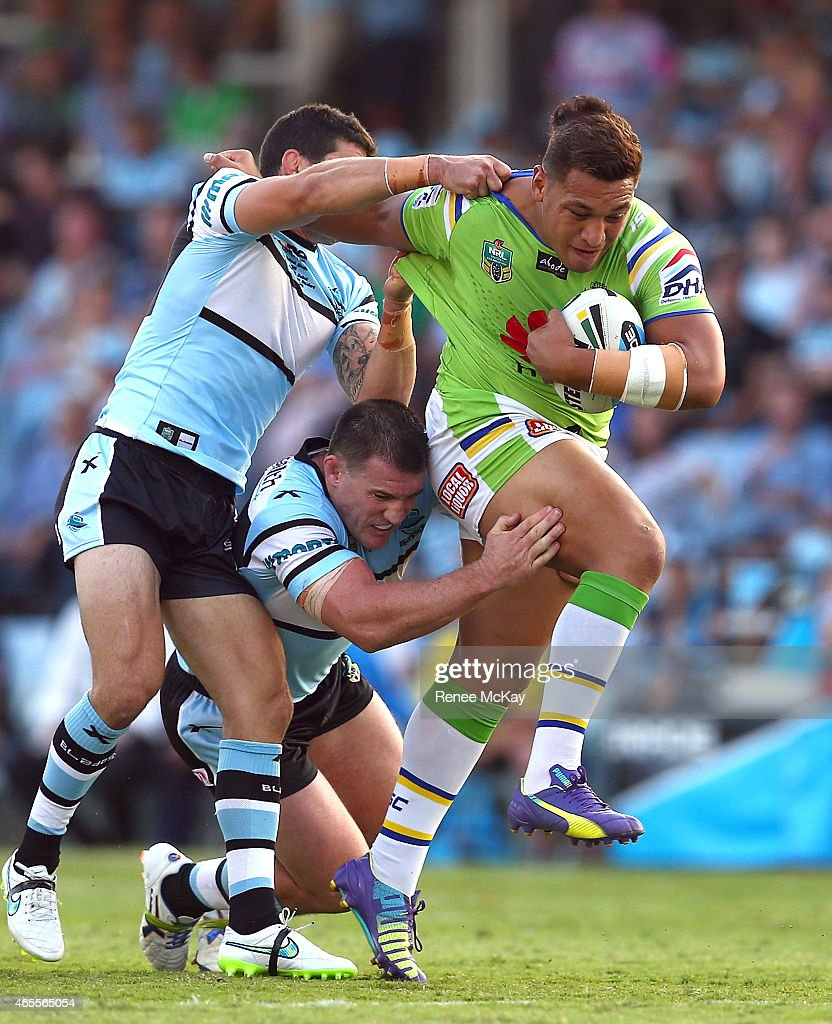 Josh Papalii of the Raiders is tackled by Michael Ennis and Paul Gallen of the Sharks during the round one NRL match between the Cronulla Sharks and the Canberra Raiders at Remondis Stadium on March 8, 2015 in Sydney, Australia.