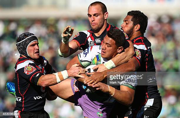 Josh Papalii of the Raiders is tackled during the round 21 NRL match between the Canberra Raiders and the New Zealand Warriors at GIO Stadium on...