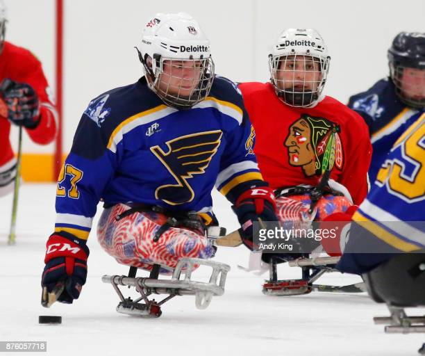 Josh Pauls of the St Louis Blues sled hockey team controls the puck in front of Kevin McKee of the Chicago Blackhawks sled hockey team during the USA...