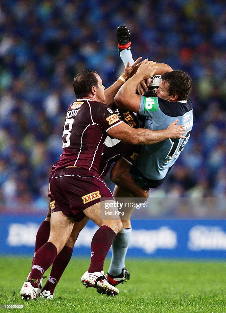 Josh Perry of the Blues is tackled heavily during game one of the ARL State of Origin series between the New South Wales Blues and the Queensland Maroons at ANZ Stadium on May 26, 2010 in Sydney, Australia.