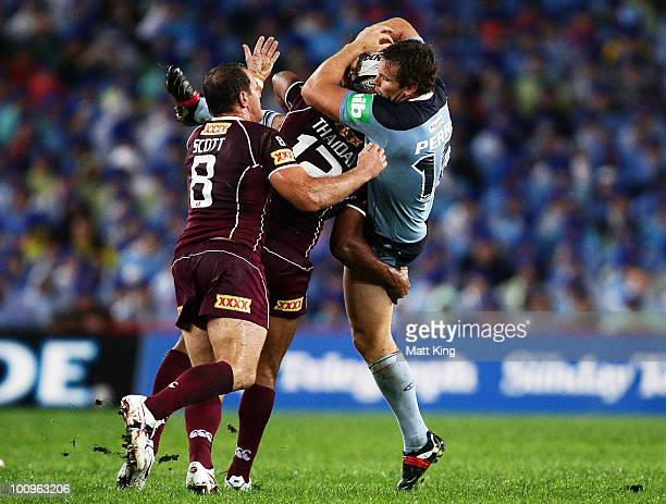 Josh Perry of the Blues is tackled heavily during game one of the ARL State of Origin series between the New South Wales Blues and the Queensland...