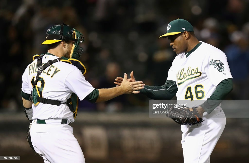 Josh Phegley #19 and Santiago Casilla #46 of the Oakland Athletics shake hands after they beat the Toronto Blue Jays at Oakland Alameda Coliseum on June 5, 2017 in Oakland, California.