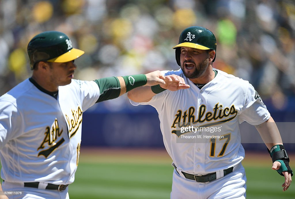 Josh Phegley #19 and Yonder Alonso #17 of the Oakland Athletics celebrates after they both scored against the Houston Astros in the bottom of the second inning at O.co Coliseum on April 30, 2016 in Oakland, California.
