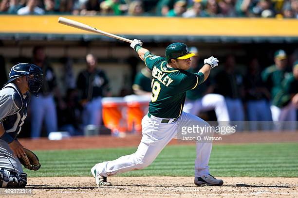 Josh Phegley of the Oakland Athletics hits an RBI single against the Seattle Mariners during the seventh inning at Oco Coliseum on April 11 2015 in...