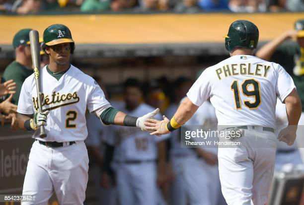 Josh Phegley of the Oakland Athletics is congratulated by Khris Davis after Phegley scored against the Texas Rangers in the bottom of the six inning...