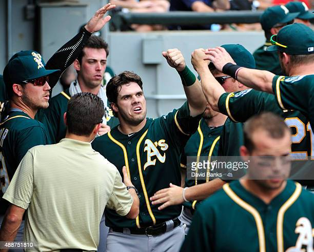 Josh Phegley of the Oakland Athletics is greeted by his teammates after scoring against the Chicago White Sox during the third inning on September 17...