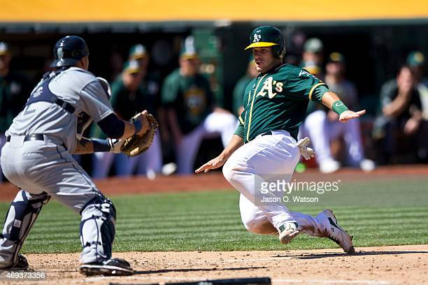 Josh Phegley of the Oakland Athletics is tagged out at home plate by Jesus Sucre of the Seattle Mariners during the seventh inning at Oco Coliseum on...