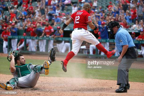 Josh Phegley of the Oakland Athletics reacts after Rougned Odor of the Texas Rangers stole home plate to score during the eighth inning at Globe Life...