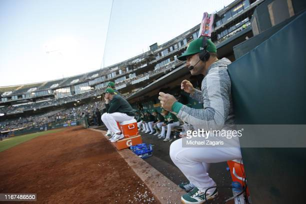 Josh Phegley of the Oakland Athletics sits in the dugout with a popcorn bag on his head, as part of a prank, during the game against the Texas...