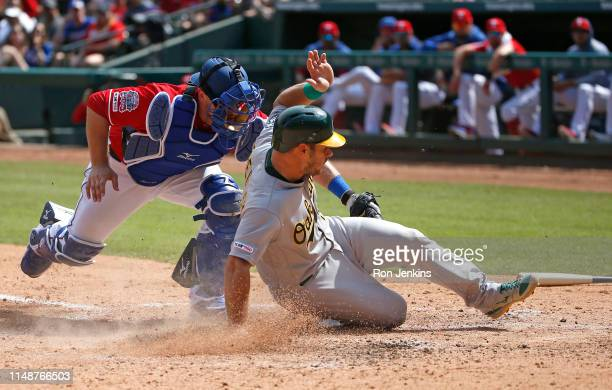 Josh Phegley of the Oakland Athletics slides into home plate ahead of the tag by Tim Federowicz of the Texas Rangers in the fourth inning at Globe...