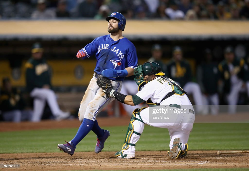 Josh Phegley #19 of the Oakland Athletics tags out Kevin Pillar #11 of the Toronto Blue Jays as he tries to score in the fifth inning at Oakland Alameda Coliseum on June 5, 2017 in Oakland, California.