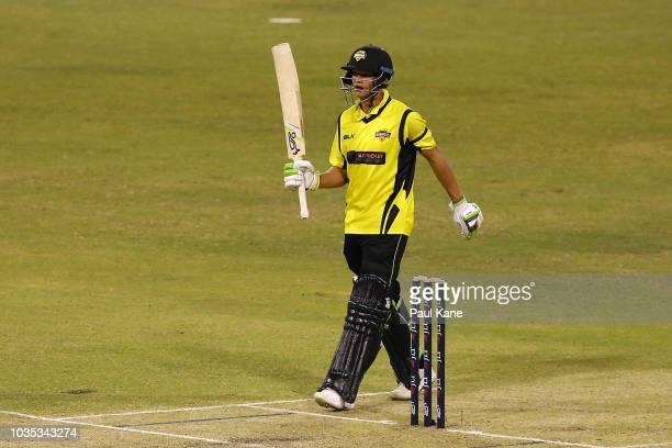 Josh Philippe of WA raises his bat to celebrate his half century during the JLT One Day Cup match between Western Australia and New South Wales at...