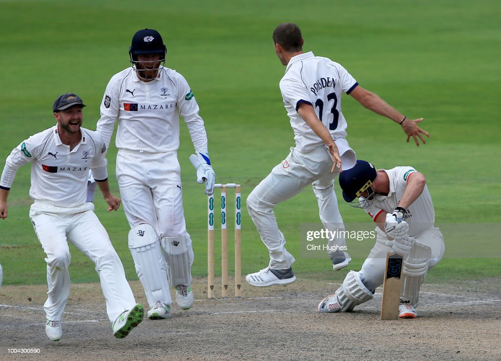 Josh Poysden (2 R) of Yorkshire celebrates after he takes the wicket of Dane Vilas (R) of Lancashire during day two of the Specsavers County Championship division one match between Lancashire and Yorkshire at Emirates Old Trafford on July 23, 2018 in Manchester, England.