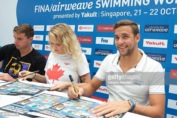 Josh Prenot of United States of America Hilary Caldwell of Canada and Chad le Clos of South Africa sign autographs during the International Swim...