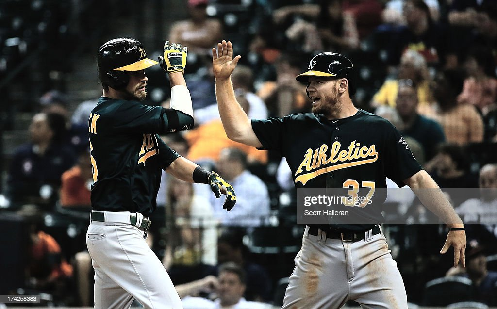 Josh Reddick #16 and Brandon Moss #37 of the Oakland Athletics celebrate after Reddick hit a two-run home run in the eighth inning against the Houston Astros at Minute Maid Park on July 22, 2013 in Houston, Texas.