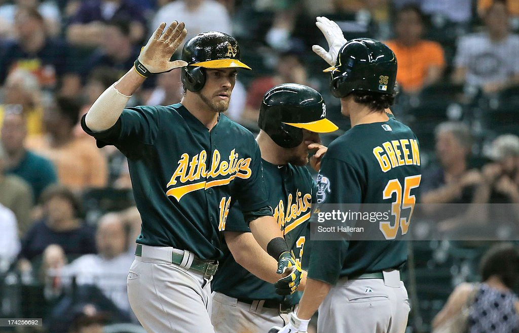 Josh Reddick #16 and Grant Green #35 of the Oakland Athletics celebrate after Reddick hit a two-run home run in the eighth inning against the Houston Astros at Minute Maid Park on July 22, 2013 in Houston, Texas.