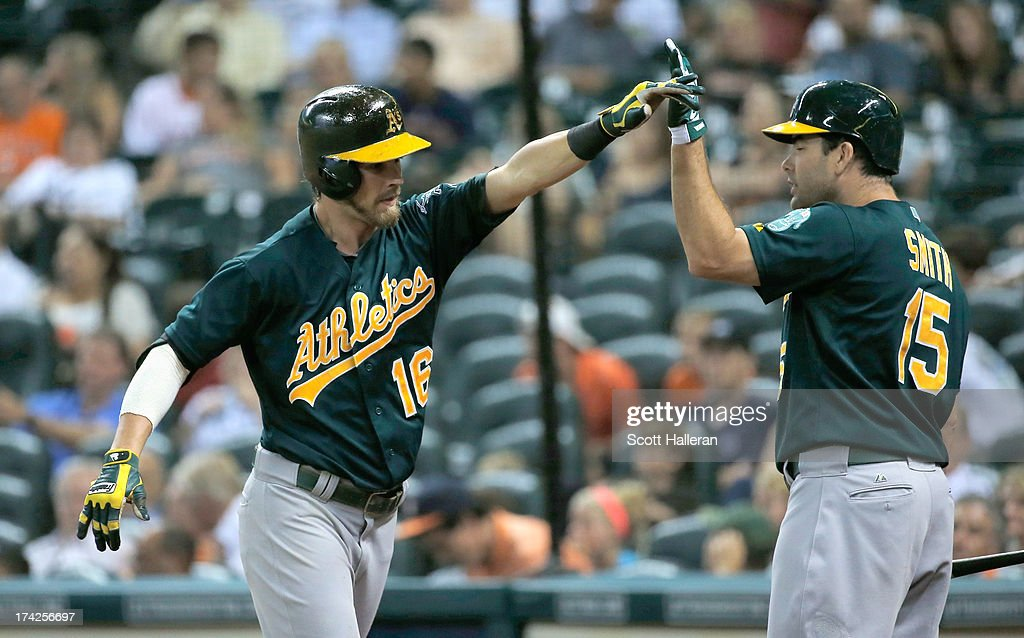 Josh Reddick #16 and Seth Smith #15 of the Oakland Athletics celebrate after Reddick hit a two-run home run in the eighth inning against the Houston Astros at Minute Maid Park on July 22, 2013 in Houston, Texas.