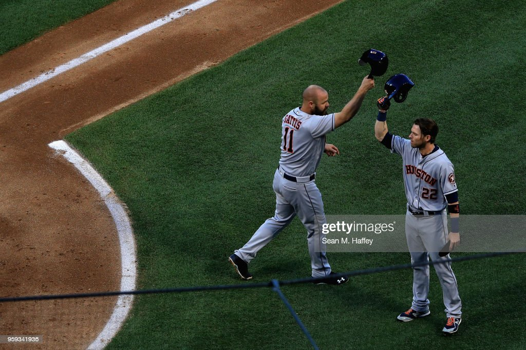 Josh Reddick #22 congratulates Evan Gattis #11 of the Houston Astros on his two-run homerun during the second inning of a game against the Los Angeles Angels of Anaheim at Angel Stadium on May 16, 2018 in Anaheim, California.
