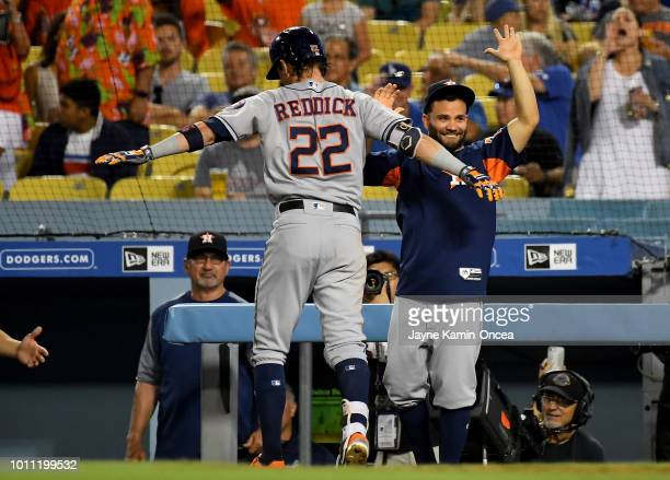 Josh Reddick is congratulated by Jose Altuve of the Houston Astros after hitting a three run home run in the eighth inning against the Los Angeles...