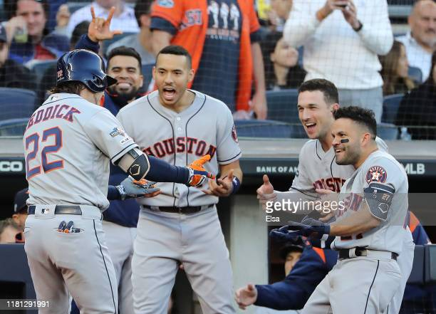 Josh Reddick of the Houston Astros celebrates at the dugout with Carlos Correa Alex Bregman and Jose Altuve after hitting a solo home run during the...