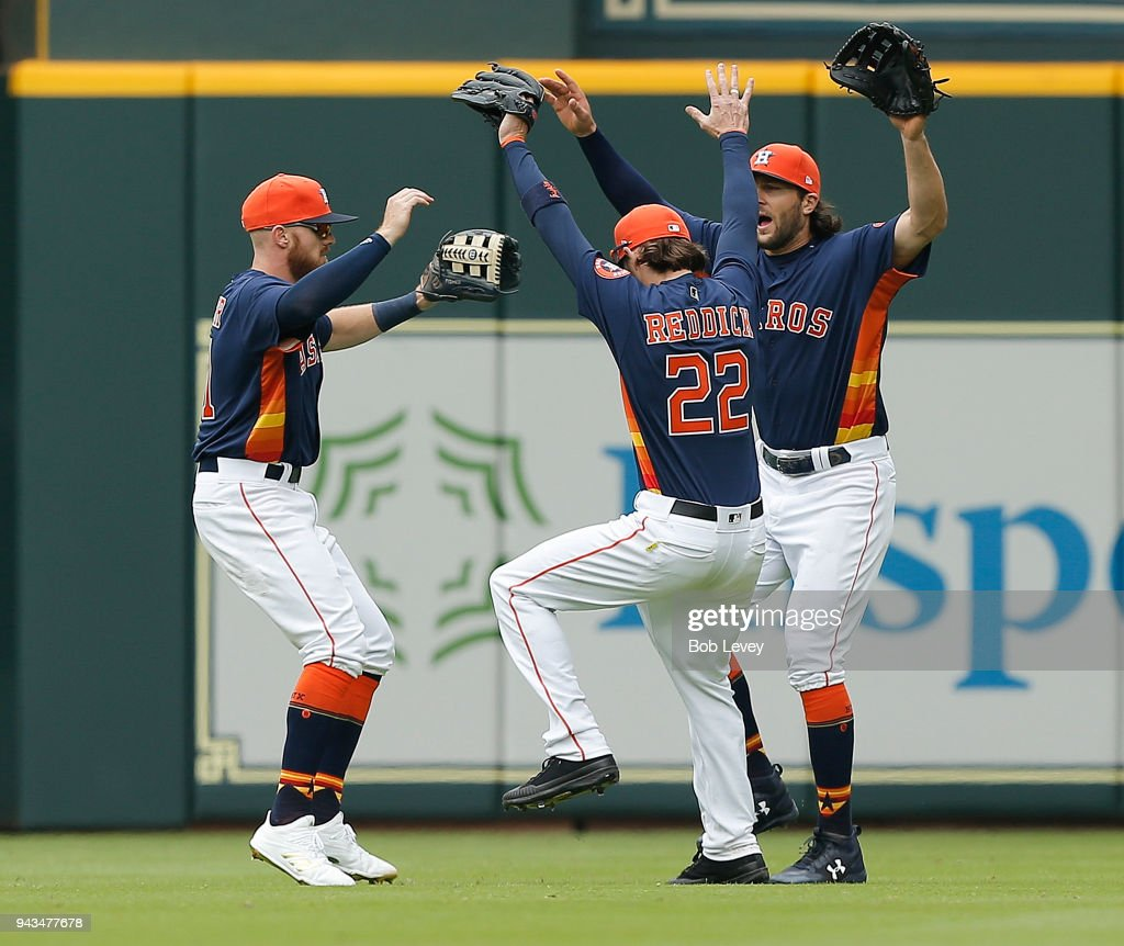 Josh Reddick #22 of the Houston Astros celebrates with Derek Fisher #21, left, and Jake Marisnick after the final out against the San Diego Padres at Minute Maid Park on April 8, 2018 in Houston, Texas.