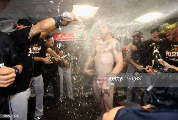 Josh Reddick of the Houston Astros celebrates with teammates in the clubhouse after defeating the Boston Red Sox 54 in game four of the American...