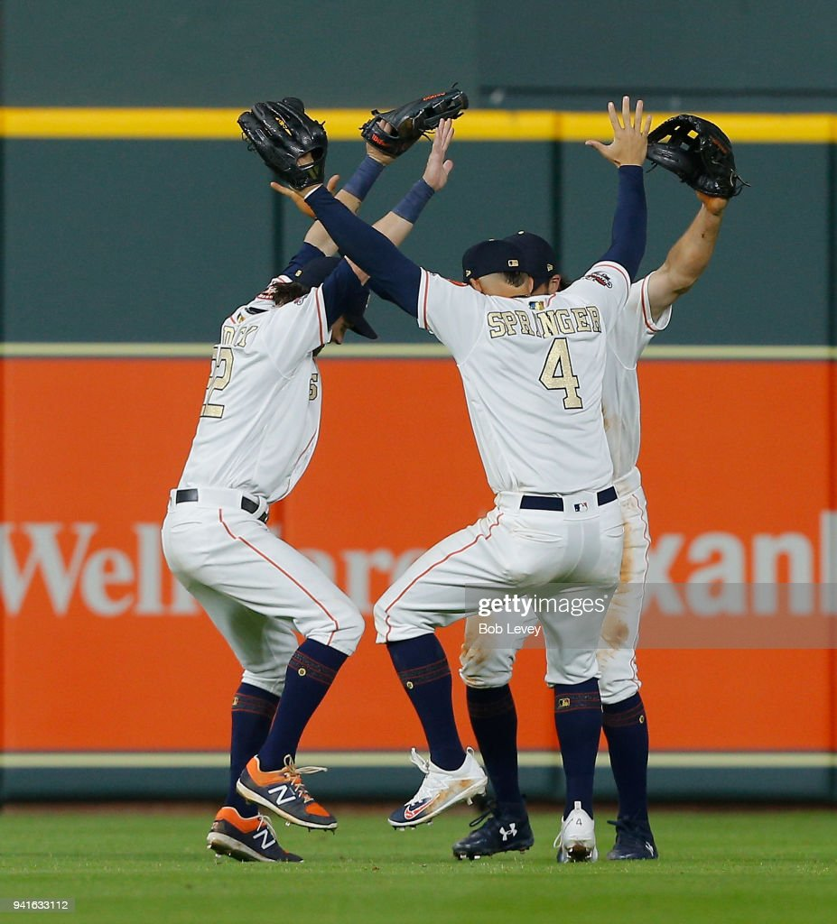 Josh Reddick #22 of the Houston Astros, George Springer #4 an Jake Marisnick #6 celebrate after a 10-6 wi over the Baltimore Orioles at Minute Maid Park on April 3, 2018 in Houston, Texas.