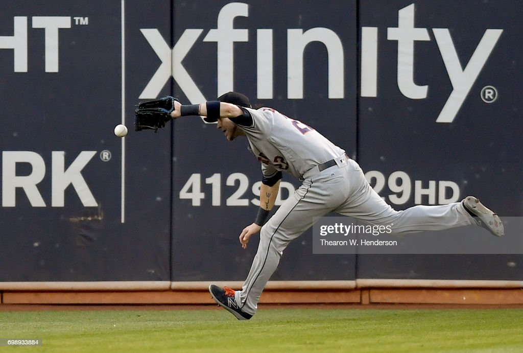 Josh Reddick #22 of the Houston Astros has the ball kick off his glove for a double off the bat of Yonder Alonso #17 of the Oakland Athletics in the bottom of the fourth inning at Oakland Alameda Coliseum on June 20, 2017 in Oakland, California.