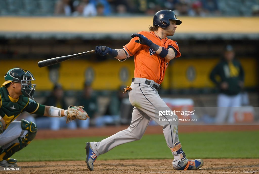 Josh Reddick #22 of the Houston Astros hits an rbi single scoring Carlos Correa #1 against the Oakland Athletics in the top of the six inning of the second game in a double header at Oakland Alameda Coliseum on September 9, 2017 in Oakland, California.