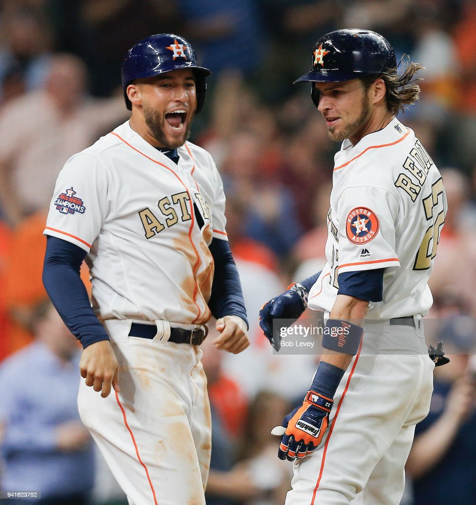 Josh Reddick #22 of the Houston Astros is congratulated by George Springer #4 after hitting a grand slam in the seventh inning against the Baltimore Orioles at Minute Maid Park on April 3, 2018 in Houston, Texas.