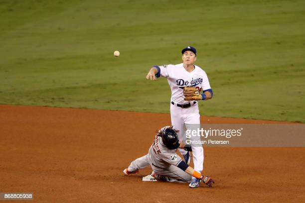 Josh Reddick of the Houston Astros is forced out at second base as Chase Utley of the Los Angeles Dodgers throws to first base during the seventh...