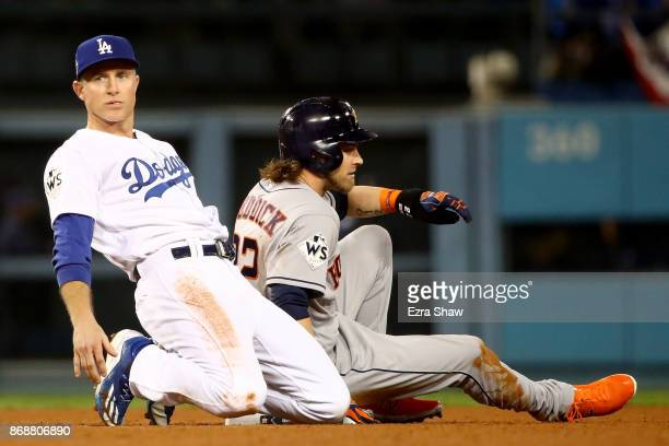 Josh Reddick of the Houston Astros is forced out at second base as Chase Utley of the Los Angeles Dodgers reacts after throwing to first base during...