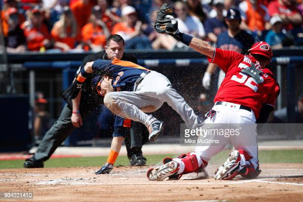 Josh Reddick of the Houston Astros is tagged out by Matt Wieters of the Washington Nationals at the plate during the first inning of a spring...
