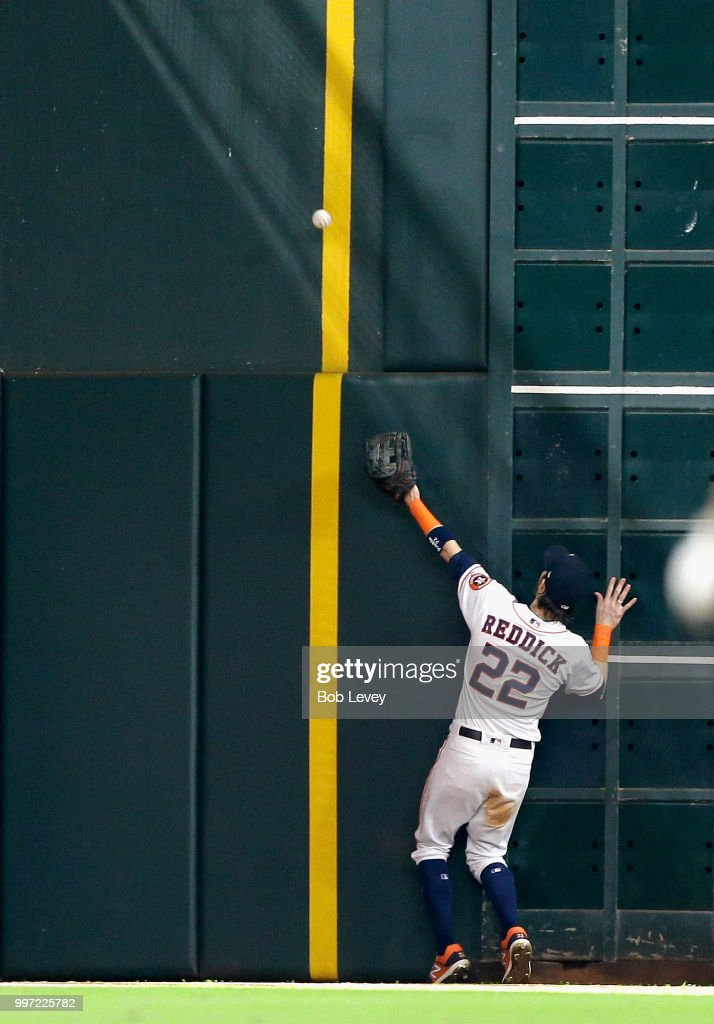 Josh Reddick #22 of the Houston Astros is unable to make a play on a ball hit by Mark Canha #20 of the Oakland Athletics in the eighth inning that scores two runs at Minute Maid Park on July 12, 2018 in Houston, Texas.