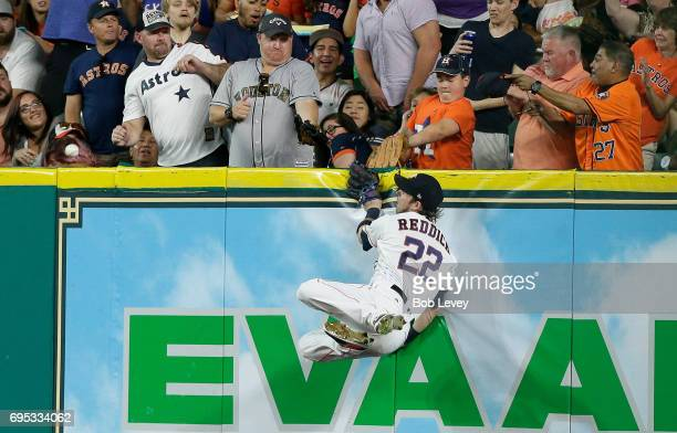 Josh Reddick of the Houston Astros leaps at the wall as he can't make a play on a line drive by Joey Gallo of the Texas Rangers in the second inning...