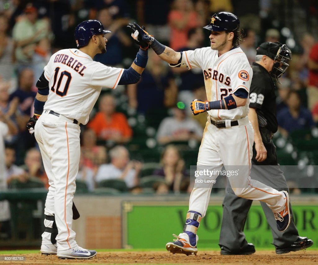 Josh Reddick #22 of the Houston Astros receives a high five from Yuli Gurriel #10 after hitting a two-run home run in the eighth inning against the Arizona Diamondbacks at Minute Maid Park on August 16, 2017 in Houston, Texas.