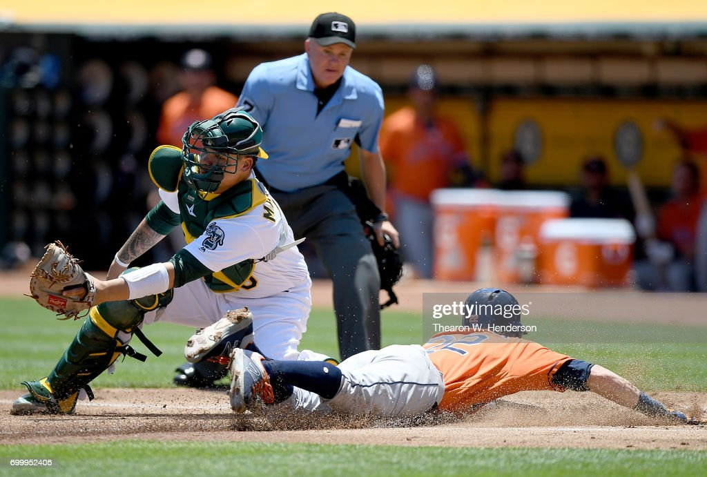 Josh Reddick #22 of the Houston Astros scores sliding past Bruce Maxwell #13 of the Oakland Athletics in the top of the first inning at Oakland Alameda Coliseum on June 22, 2017 in Oakland, California.