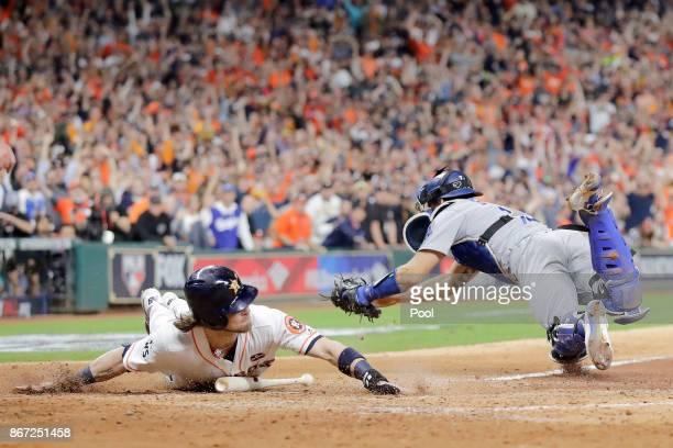 Josh Reddick of the Houston Astros slides in to home plate beating the tag of Austin Barnes of the Los Angeles Dodgers during the fifth inning in...
