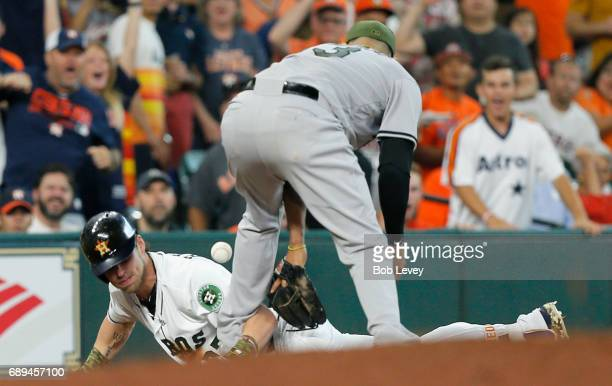 Josh Reddick of the Houston Astros triples in the second inning as Manny Machado of the Baltimore Orioles bobbles the throw at Minute Maid Park on...