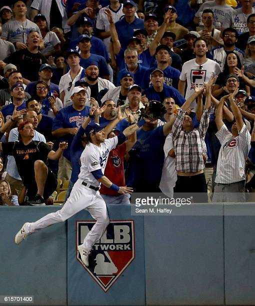 Josh Reddick of the Los Angeles Dodgers attempts to make a catch in the stands in the fifth inning on a ball hit by Ben Zobrist of the Chicago Cubs...