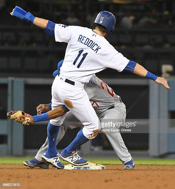 Josh Reddick of the Los Angeles Dodgers is caught stealing and tagged out by Addison Russell of the Chicago Cubs in the eighth inning at Dodger...