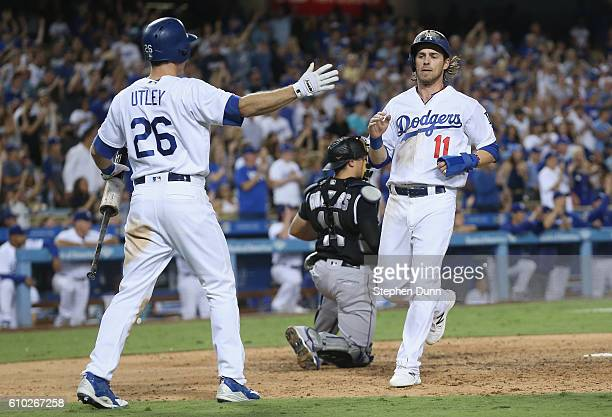 Josh Reddick of the Los Angeles Dodgers is greeted by on deck batter Chase Utley after scoring a run in the fifth inning against the Colorado Rockies...