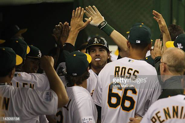 Josh Reddick of the Oakland Athletics celebrates with team mates after hitting a home run in the seventh inning against the Seattle Mariners during...