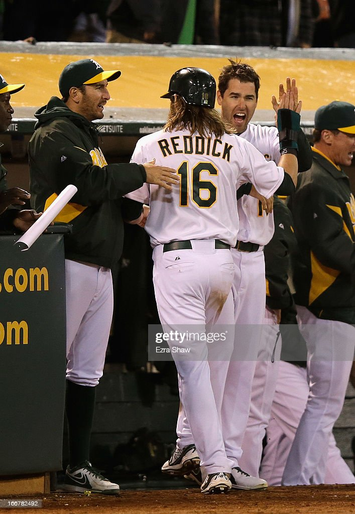Josh Reddick #16 of the Oakland Athletics is congratulated by Seth Smith #15 (left) after he scored the go ahead run in the eighth inning against the Houston Astros at O.co Coliseum on April 16, 2013 in Oakland, California.
