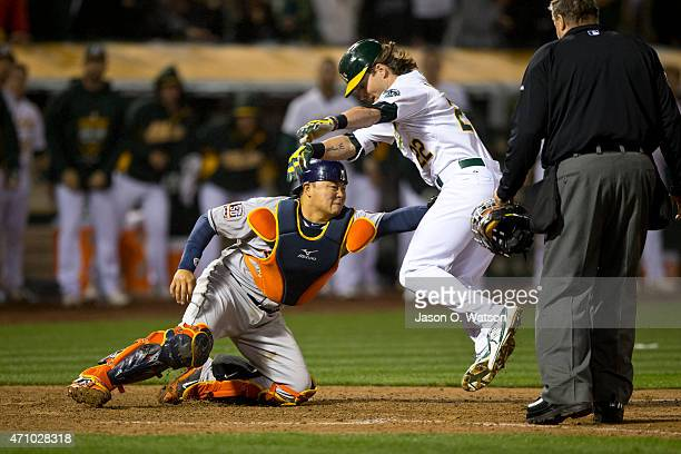 Josh Reddick of the Oakland Athletics is tagged out at home plate by Hank Conger of the Houston Astros during the tenth inning at Oco Coliseum on...