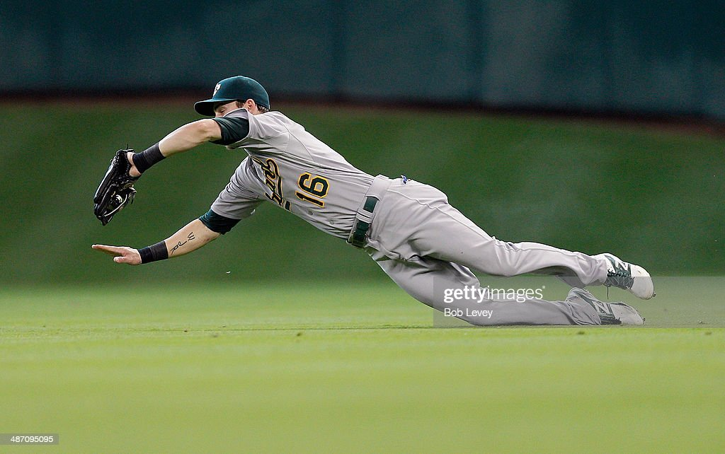 Josh Reddick #16 of the Oakland Athletics makes a diving catch on a soft line drive by Matt Dominguez #30 of the Houston Astros in the second inning at Minute Maid Park on April 27, 2014 in Houston, Texas.