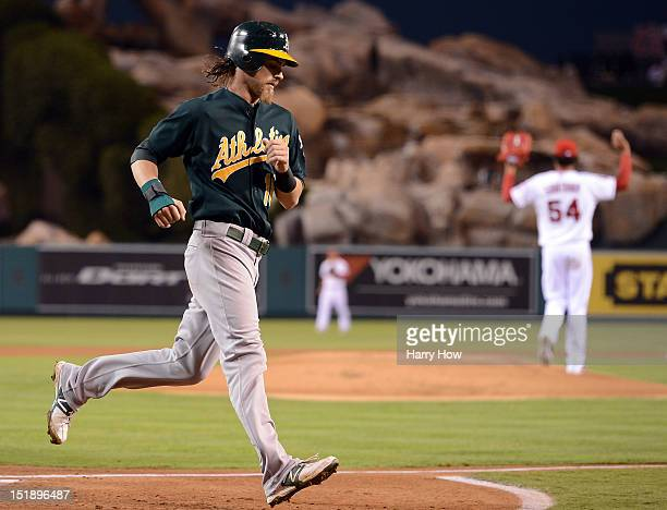 Josh Reddick of the Oakland Athletics scores a run off of a fielding error for a 10 lead in front of Ervin Santana of the Los Angeles Angels during...