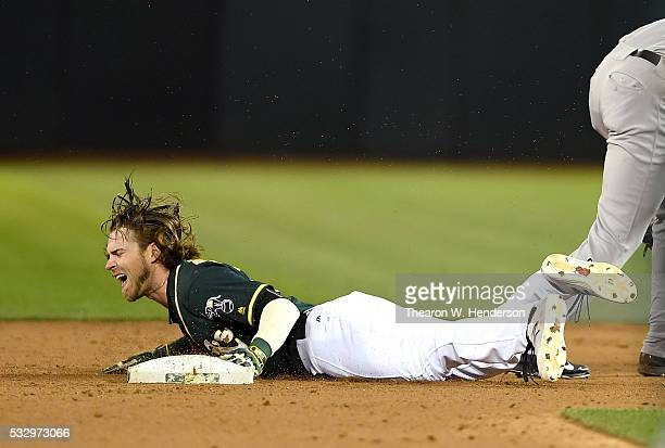 Josh Reddick of the Oakland Athletics steals second base but reacts in pain after he was kicked in the head by a leaping Starlin Castro of the New...